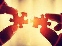 photo of person fitting puzzle pieces together